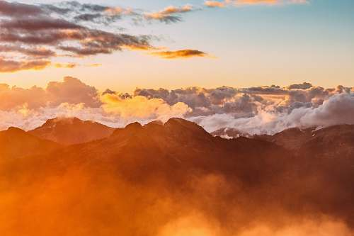 nature landscape photography of mountains with cloudy skies during golden hour sunset