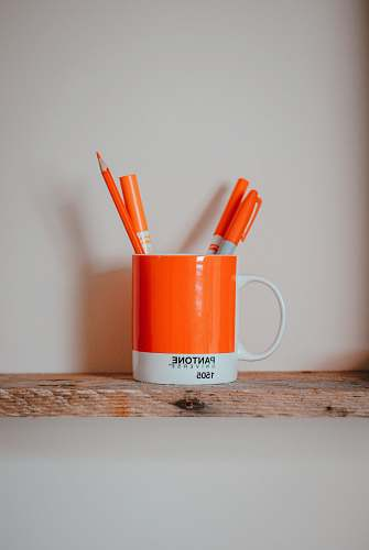 food markers in mug on brown surface cup