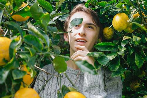 citrus fruit man holding his jaw surrounded by yellow fruit flora