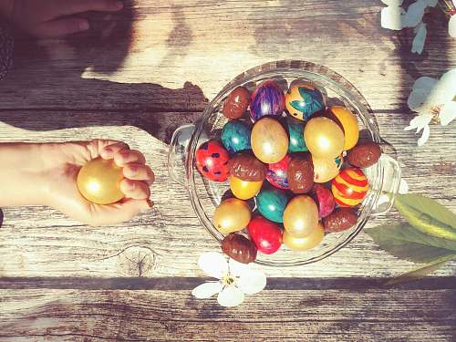 egg bowl of assorted-color Easter eggs person