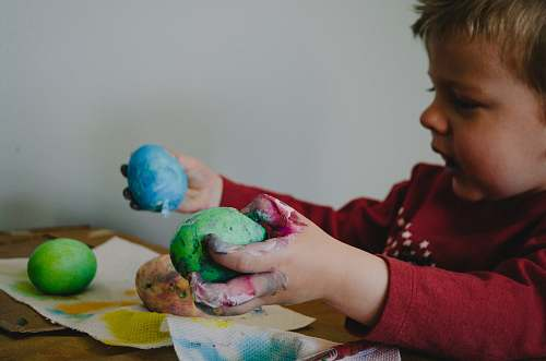 people boy holding blue and green painted egg shells person