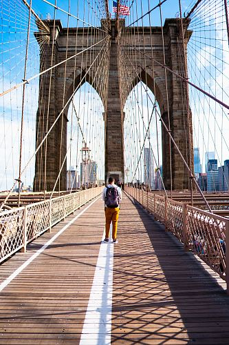 photo an in white shirt and yellow pants walking on bridge during daytome free for commercial use images