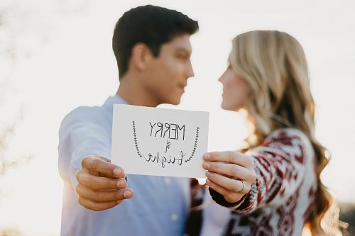 couples holding Merry & Bright card