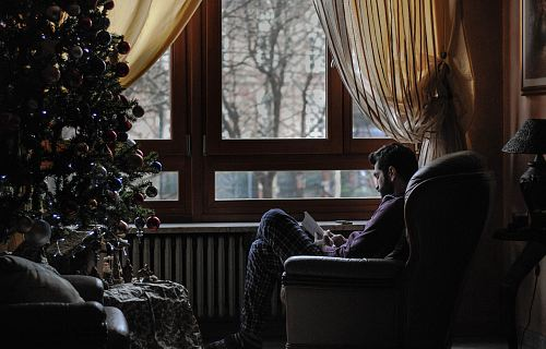 man sitting on sofa chair near Christmas tree