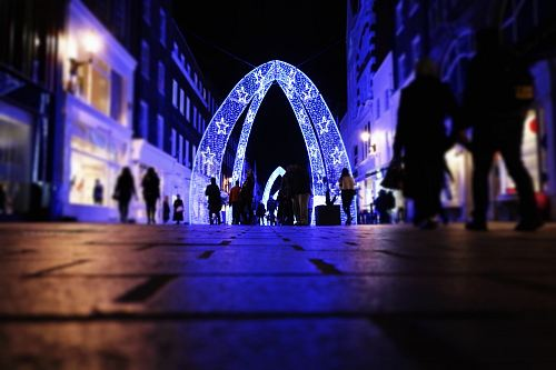 people walking near arched lighted decor between buildings