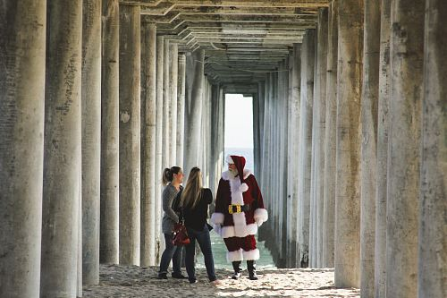 Santa Claus talking to woman near concrete post