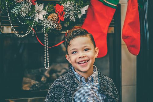 photo smiling boy in gray inner shirt and gray cardigan standing by fireplace with decors free for commercial use images
