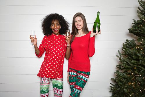 photo woman holding wine bottle while another woman holding two clear wine glasses free for commercial use images