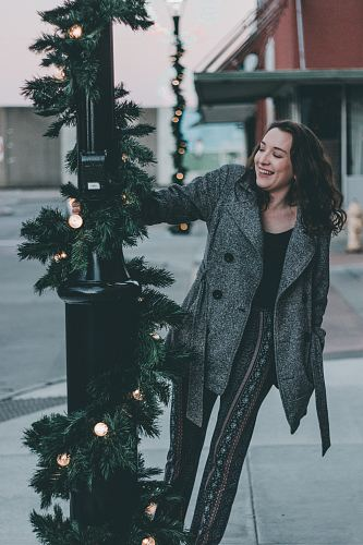 woman in gray coat holding post light