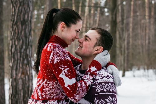woman wearing red and white fair-isle knit sweater hugging man wearing brown and red fair-isle sweater