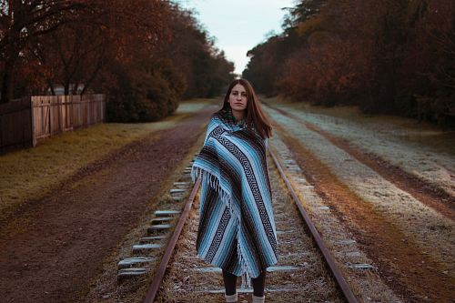 photo woman with blue and black striped scarf standing on brown train railway during daytime free for commercial use images