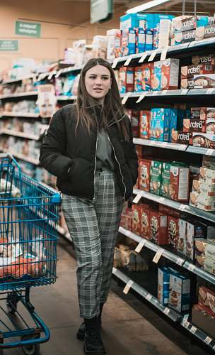 jacket woman standing near shopping cart and groceries inside warehouse coat