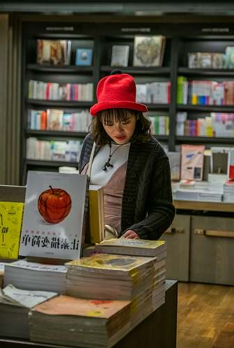 indoors woman with red hat checking books on display clothing