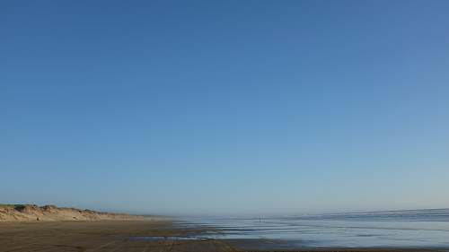 ocean body of water and gray seashore under blue sky blue