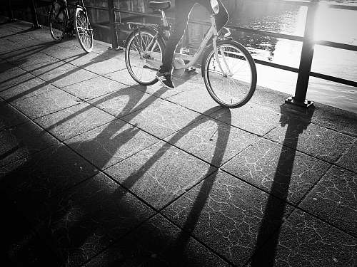 bicycle grayscale photo of a person wearing sneakers riding a bicycle bike
