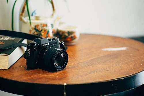 tabletop black DSLR camera on top of brown wooden table fujifilm camera