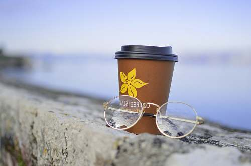 corfu gold-colored framed eyeglasses beside plastic disposable cup greece
