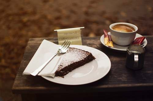 food plate of sliced cake with silver fork beside cup of coffe on brown wooden serving board dessert