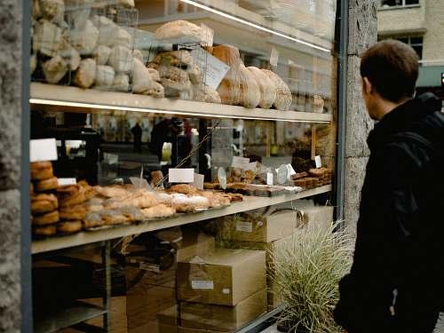 bakery man wearing black jacket standing near glass window bread