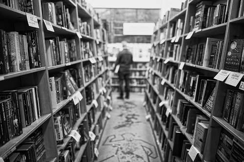 person grayscale photo of man standing in front of books black-and-white