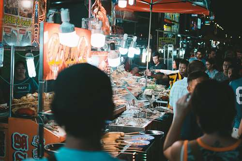 person group of people standing beside stall market