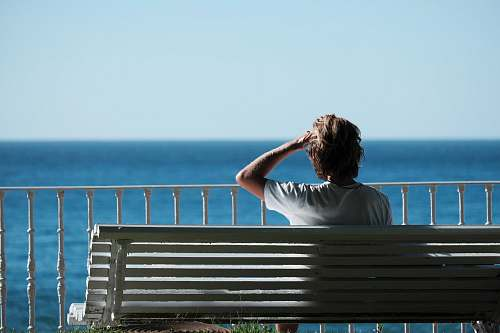 people man sitting on bench near body of water during daytime person
