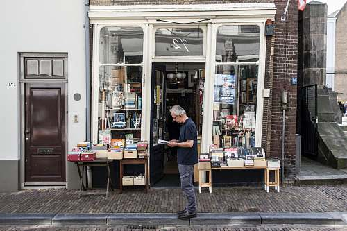 person man standing in front of a bookshop indoors