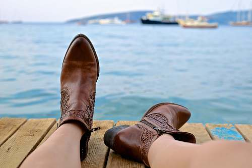 sea person wearing brown leather side-zip boots sits on brown wooden pier near body of water during daytime boot