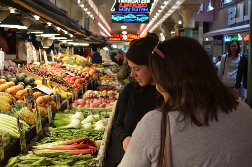person two woman standing beside vegetable display grocery store