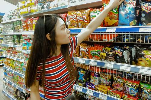 person woman standing while grabbing plastic pack grocery store