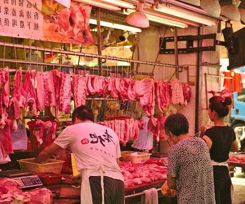 human man and woman vending raw meats butcher shop