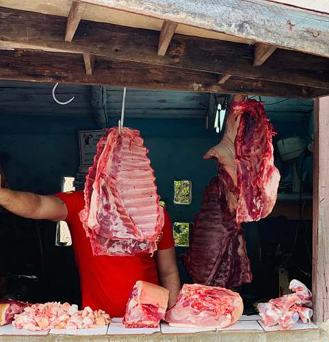 butcher shop man standing in front of hanged meat shop