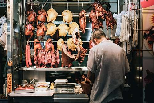 human man standing on store butcher shop
