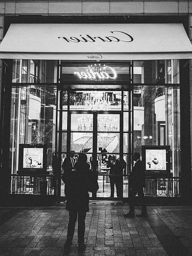 human person standing front of Cartier signage black-and-white