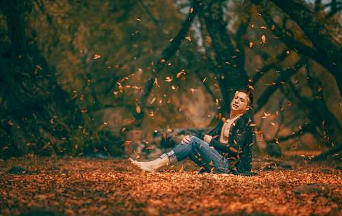 human shallow focus photography of man sitting on brown dried leaves surrounded by trees during daytime people