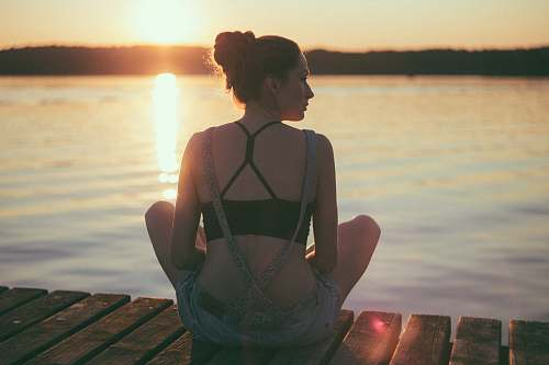 human woman sitting on brown wooden dock during sunset people