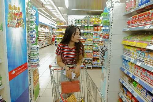 human woman standing between gondola shelves market