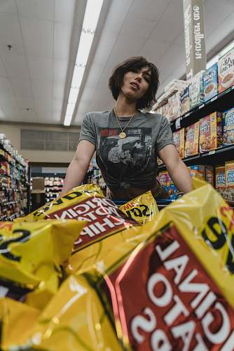 human woman standing in front of chip bags inside store grocery store