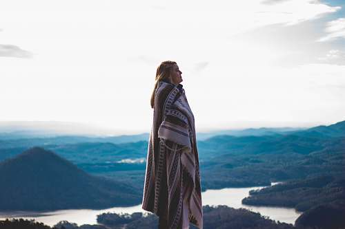 human woman wearing coat standing on cliff people