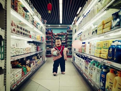 supermarket baby walking between white shelves market