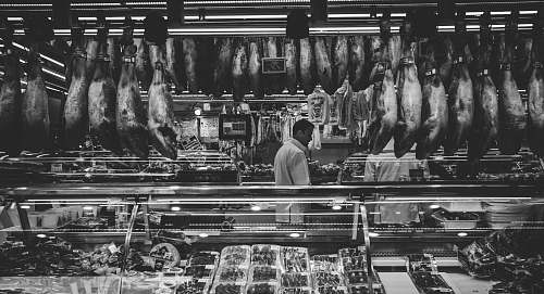 black-and-white grayscale photography of man standing in store butcher shop