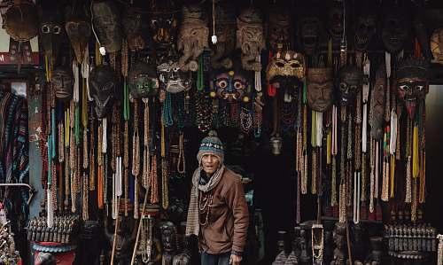 market man in brown jacket standing below hanging decors bazaar