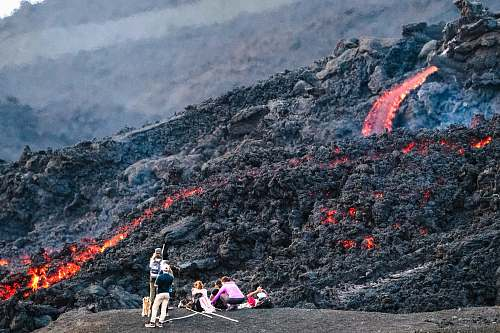 mountain photography of people standing beside lava during daytime outdoors