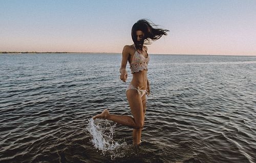 A girl in a bikini flicks her leg up behind her in the water at a beach