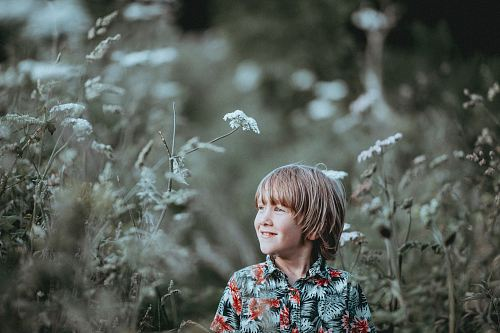 photo boy's red and green floral button-up collared top smiling facing grasses free for commercial use images
