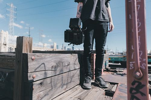 photo man holding black video camera while standing on plank free for commercial use images