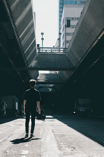 man walking under the bridge
