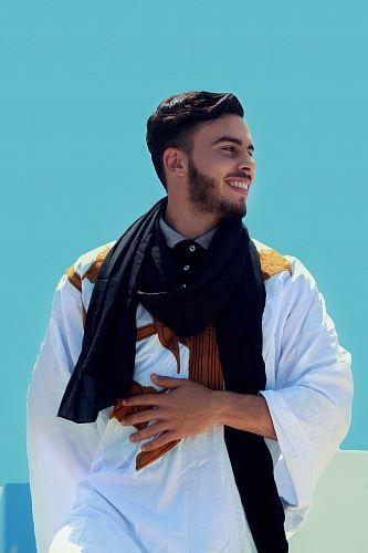man wearing black shawl touching stomach