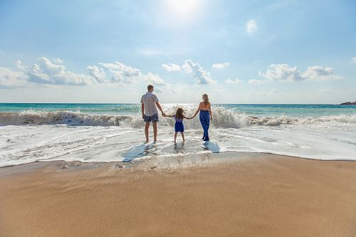 photo man, woman and child holding hands on seashore free for commercial use images