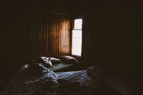 photo Pale light pouring into a cabin through a small window illuminates two unmade beds free for commercial use images